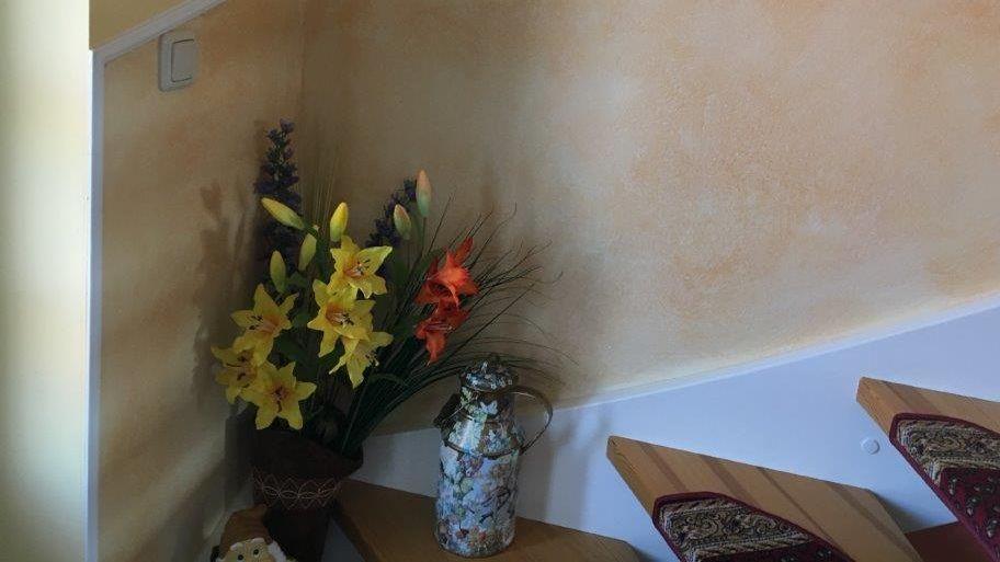 wohnliches Treppenhaus mit Blumenstrauß, Teppichbelag auf den Treppenstufen